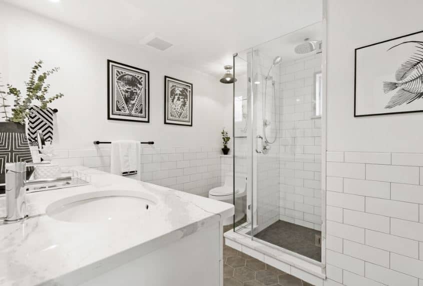 The wall-mounted black and white photos give accent to the white walls and white ceiling of this simple white bathroom. The white toilet is topped with ceiling-mounted semi-flush lighting that matches the hexagonal gray tiles of the floor.