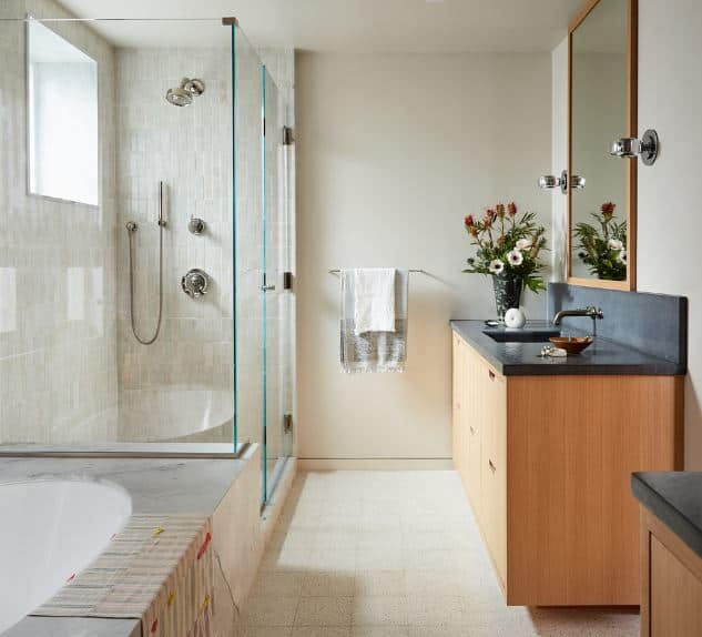 The floating wooden cabinets and drawers of the vanity area are topped with a black stone countertop extending to the backsplash. The wall-mounted mirror above the backsplash has a wooden frame and is flanked by two modern metallic lamps.