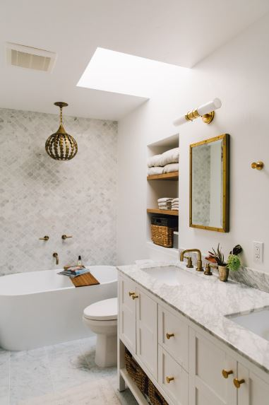 The white bathtub at the corner is topped with a pendant light that has a chic brass design matching with the faucets and bathroom fixtures. There is a sunroof over the white toilet beside the vanity area that has white wooden drawers and a shelf at the bottom.