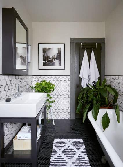 The patterns of the white-tiled walls and the black-tiled floor complement each other and contribute to the simple intricacy of the bathroom. This is contrasted by potted plants that pop out against the white freestanding bathtub and white sink.