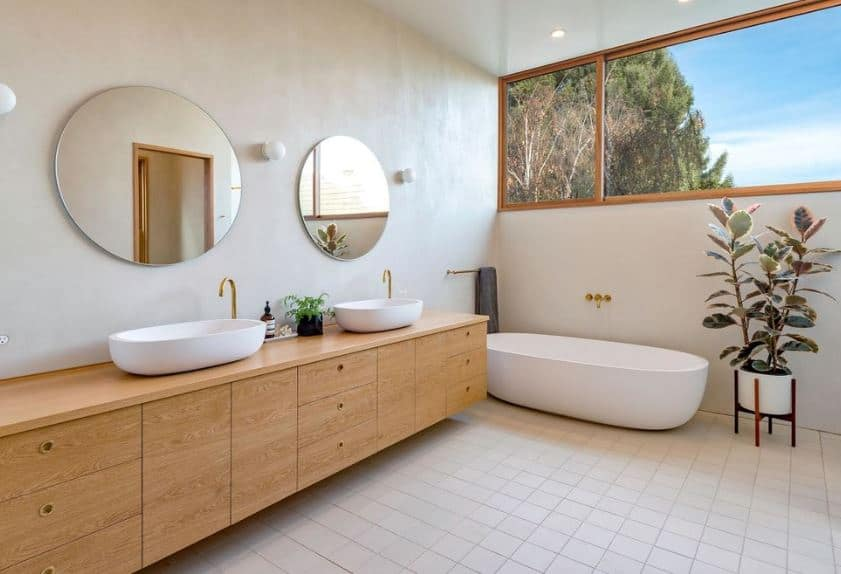 This airy bathroom has a long floating vanity area that is wide enough for two sinks with their own golden faucets and wall-mounted circular mirrors. The freestanding bathtub at the corner is topped with a wide glass window illuminating the white-tiled flooring.