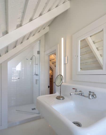 This Scandinavian-Style bathroom has a low wooden shed ceiling that has white exposed wooden beams. There is a simple floating white sink by the door. The glass door leading to the white-tiled shower area follows the lay of the shed ceiling.