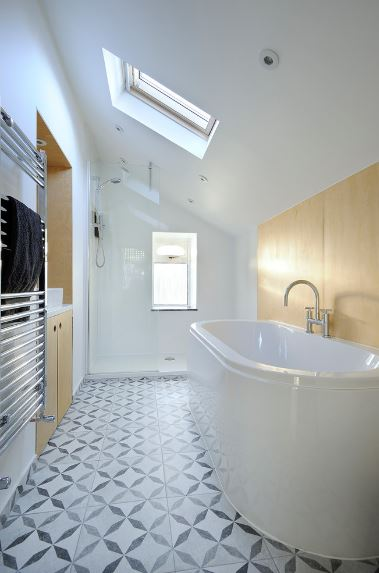 The white shed ceiling of this Scandinavian-Style bathroom has a sunroof that looks over the white bathtub that takes up most of the space of the wooden wall. To save space, The wooden vanity area is embedded into the wall across from the bathtub.