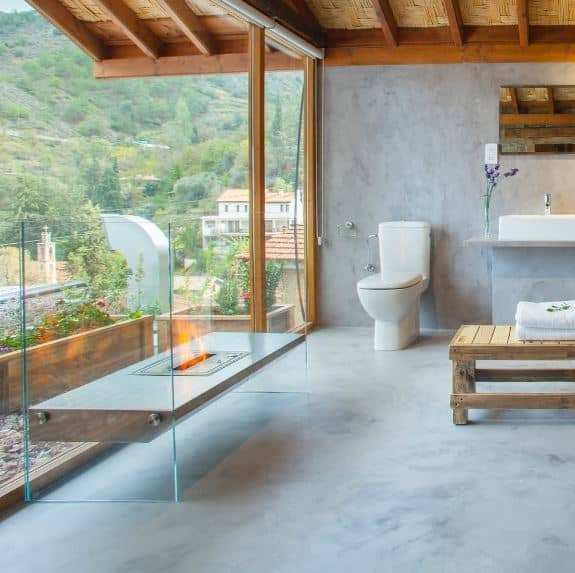 This a bright and airy bathroom with glass walls opening up to the rooftop garden. This is paired with a glass-mounted modern fireplace that offers warmth to the wide gray floors and rustic wooden ceiling with woven wicker and exposed beams.