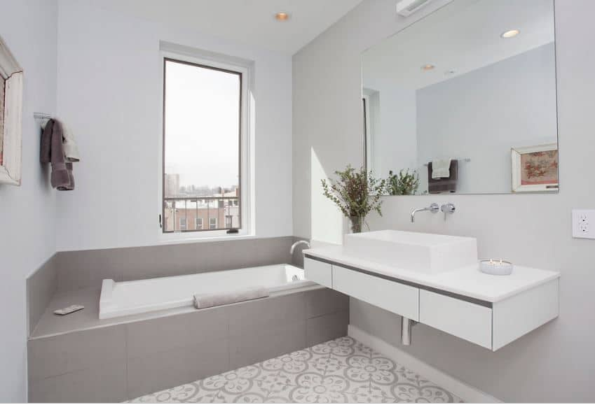 The white bathtub is fixed into a charming cove beside the window with gray tiles that match the gray patterns of the floor tiles and complements the light gray walls. The floating white vanity area has a white sink paired with a wide rectangular frame-less mirror.