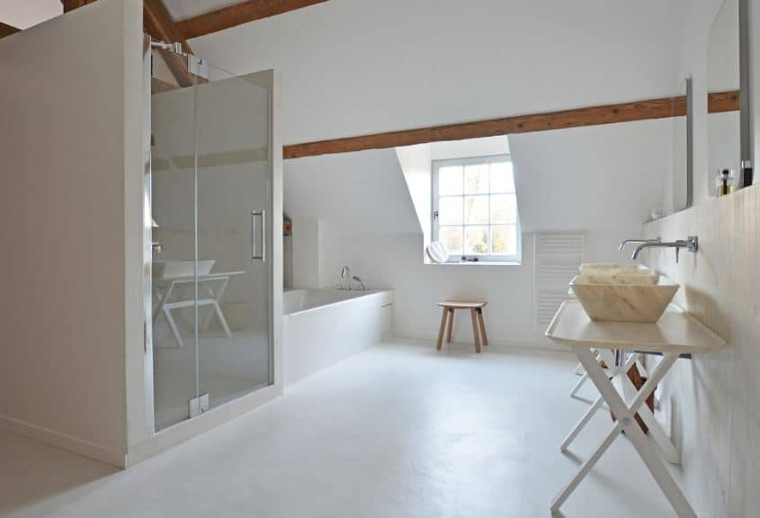 The natural light coming in from the dormer window of this Scandinavian-Style bathroom illuminates the white flooring and white shed ceiling with exposed wooden beams. beside the window is a white bathtub fixed into the corner.