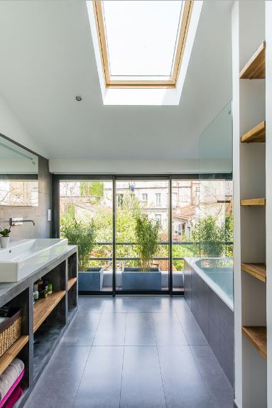 The entire wall at the head of the bathtub is made of glass that offers a view of the row of potted plants outside. The natural light of this glass wall is supplemented by the sunroof on the white ceiling. Contrasting this brightness are the dark gray tiles of the floor and built-in shelves of the vanity area.