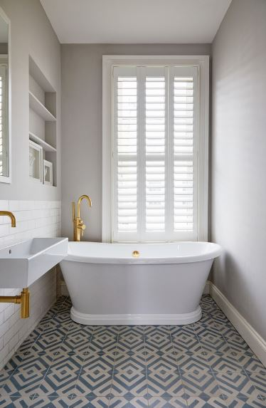 The floor tiles of this Scandinavian-Style bathroom has intricate sea-green patterns that contrast the white freestanding bathtub paired with a golden faucet. This matches with the golden faucet and fixtures of the white sink illuminated by a white shuttered window.