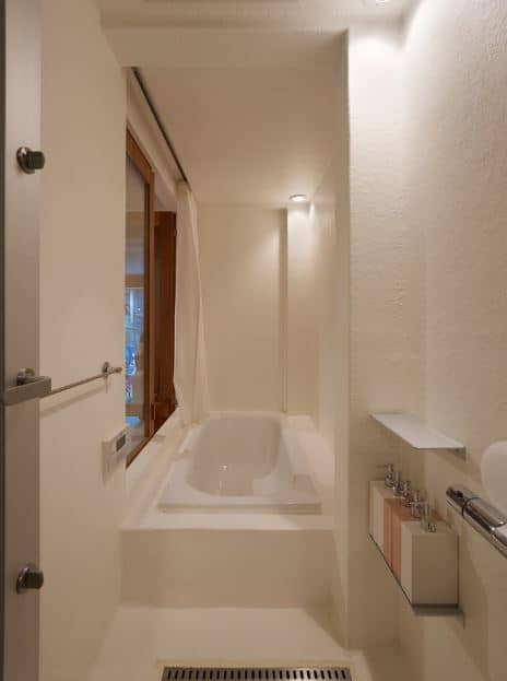 This is a small Scandinavian-Style bathroom that maximizes its small floor space with a white bathtub fixed into a cove of the beige ceiling, beige walls, and glass windows framed with wood. The corner is illuminated by ceiling mounted pin lights.