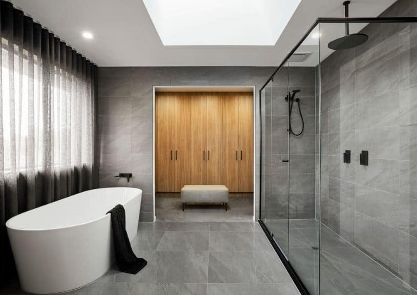 The Scandinavian-Style bathroom is dominated by gray tones of the floor tiles that extend to the walls. The shower area is separated from the rest of the room by sliding glass doors framed with black that matches the bathroom fixtures.