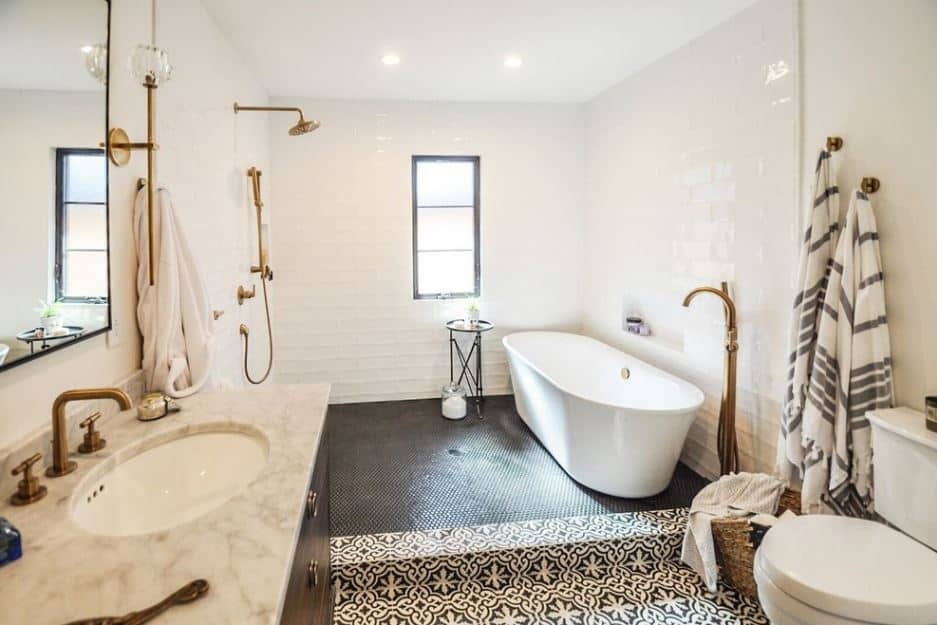 The white freestanding tub is in the shower area both over small black tiles that contrast the white tiles of the walls and ceiling. The flooring of the toilet and vanity area is patterned black and white that contrasts the wooden vanity with a brass faucet.