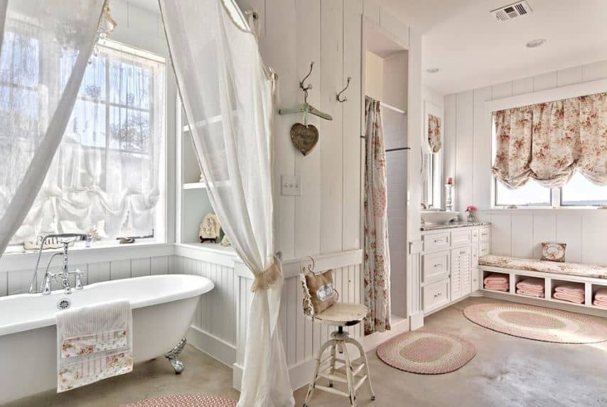 This spacious bathroom has enough space for a large freestanding bathtub in an alcove of wooden shelves and curtained windows as well as a shower area with a floral shower curtain matching the curtains above the sitting area.
