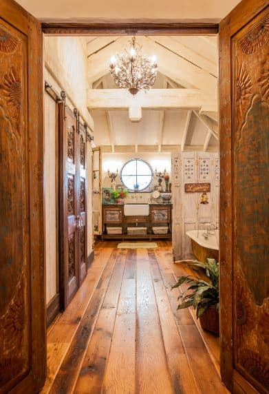 The cathedral wooden ceiling has exposed wooden beams reminiscent of a barn. This is adorned with the yellow lights of the intricate chandelier hanging over the hardwood flooring paired with a wooden vanity and a brown bathtub.
