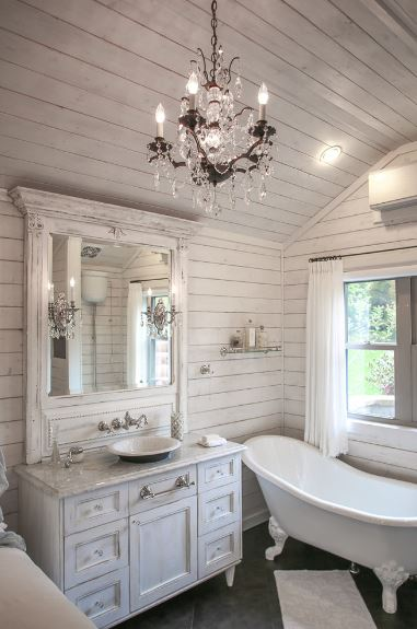 The white shiplap finish of the cathedral ceiling extends to the walls that serve as a charming background for the white freestanding bathtub and the white vanity with a mirror accented with wall lamps that match the chandelier above.