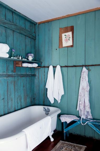 The white wooden plank walls have a delightful green hue with a distressed finish that provides a charming background for the white porcelain freestanding bathtub that contrasts the dark hardwood flooring.