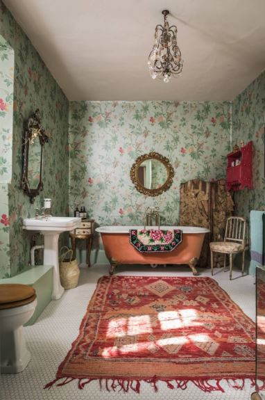 This large bathroom has small white floor tiles covered with a red patterned area rug that contrasts the green floral wallpaper that emphasizes the orange freestanding bathtub and the white pedestal sink as well as their wall-mounted mirrors.