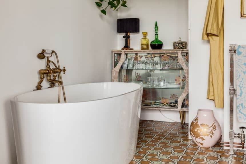 The flooring is dominated by patterned brown and white tiles that makes the white freestanding bathtub stand out. It has elegant brass fixtures that stand out against the white walls adorned with a glass cabinet filled with wine and glasses.