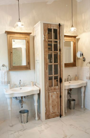 The two white sinks with pencil legs are flanking a narrow wooden cabinet that matches the wooden framed vanity mirrors topped with a pendant light casting warm yellow light on the light beige walls.