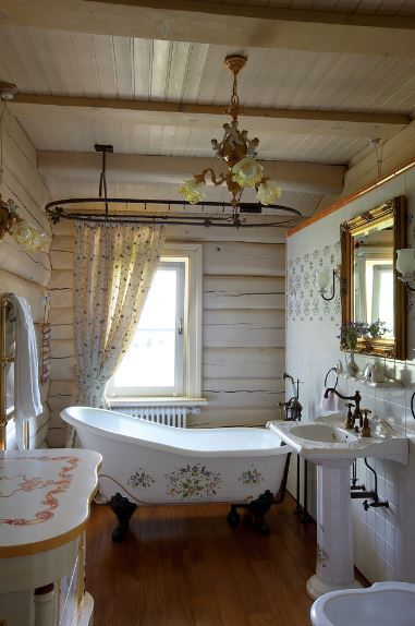 The beautiful freestanding bathtub has a floral design on its side that matches the designs of the white vanity and the elegant chandelier hanging from the wooden ceiling with exposed wooden beams contrasting the dark hardwood flooring.