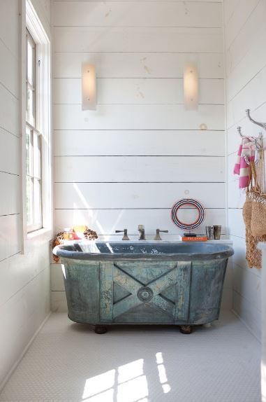 The gorgeous industrial-style green bathtub is the highlight of this bathroom. This bathtub stands out against the white flooring, walls and ceiling all illuminated by a brilliant white window by the head of the tub.