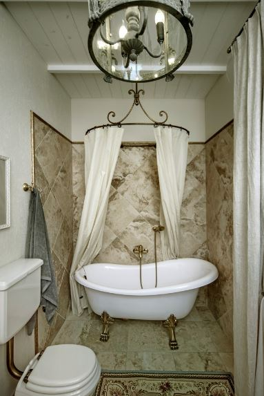 The small white freestanding bathtub inside a small alcove of beige marble walls and floor has beautiful golden legs that match the fixtures as well as the pipes of the white toilet under a farmhouse-style chandelier.