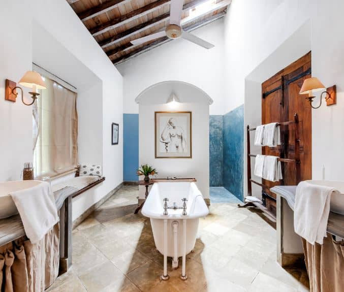 The wooden shed ceiling has exposed wooden beams supporting a ceiling fan over the white freestanding bathtub in the middle of the beige-tiled flooring leading to a shower area at the far wall covered with a white wall.