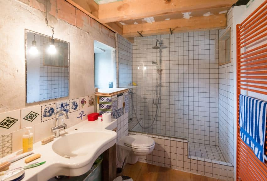 This small and simple bathroom has a shower area on the far wall with white tiles extending to the wall of the floating toilet beside the large sink with its own built-in countertop paired with a wall-mounted mirror and an industrial-style pendant light.
