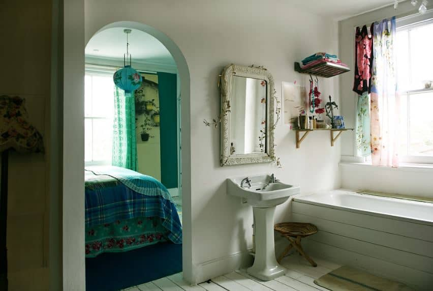 the beautiful vanity mirror has a white carved frame adorned with flowers and vines complementing the white walls and white pedestal sink beside the bathtub that is inlaid with white tiles same as the flooring.