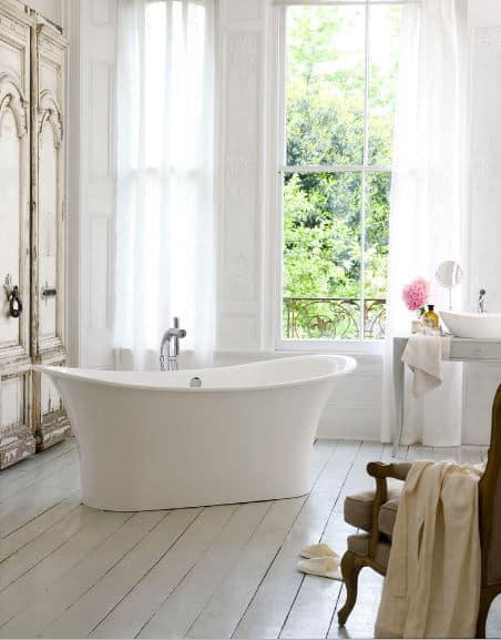 The white freestanding bathtub is placed in a quaint corner by the curtained tall windows that bring in an abundance of natural lighting on the white wooden flooring complementing the light gray table supporting the white sink.