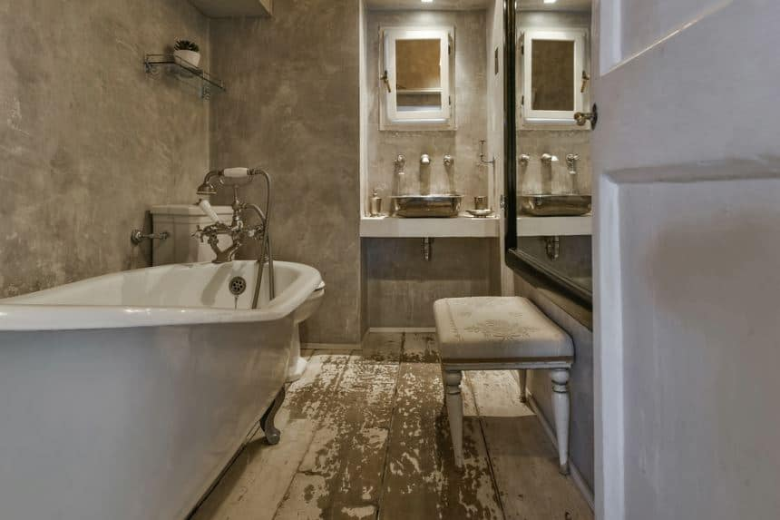 The distressed white wooden flooring is a nice charming background for the sleek white freestanding bathtub paired with silver fixtures matching the legs of the tub and the freestanding stainless steel basin of the sink on the far wall.