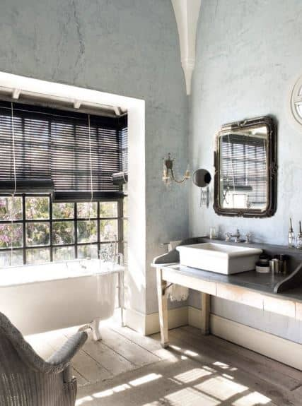 The hardwood flooring that is covered with a woven area rug is illuminated by the sunlight coming in from the French windows with black blinds by the freestanding bathtub. Adjacent to it is the white sink on a wooden table perfect for the light hued walls.
