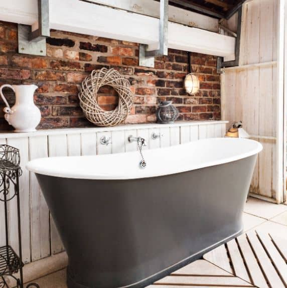The gorgeous freestanding tub has a matte black facade contrasting its sleek porcelain inner basin complemented by the white wooden shiplap lower wall contrasting the red brick upper wall adorned with decors and a white exposed beam.
