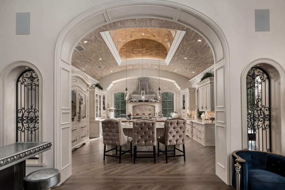 A view of the luxury kitchen through the open archway boasting white cabinets and an island paired with taupe tufted chairs. It is illuminated by recessed lights and glass pendants that hung from the marvelous tray ceiling.