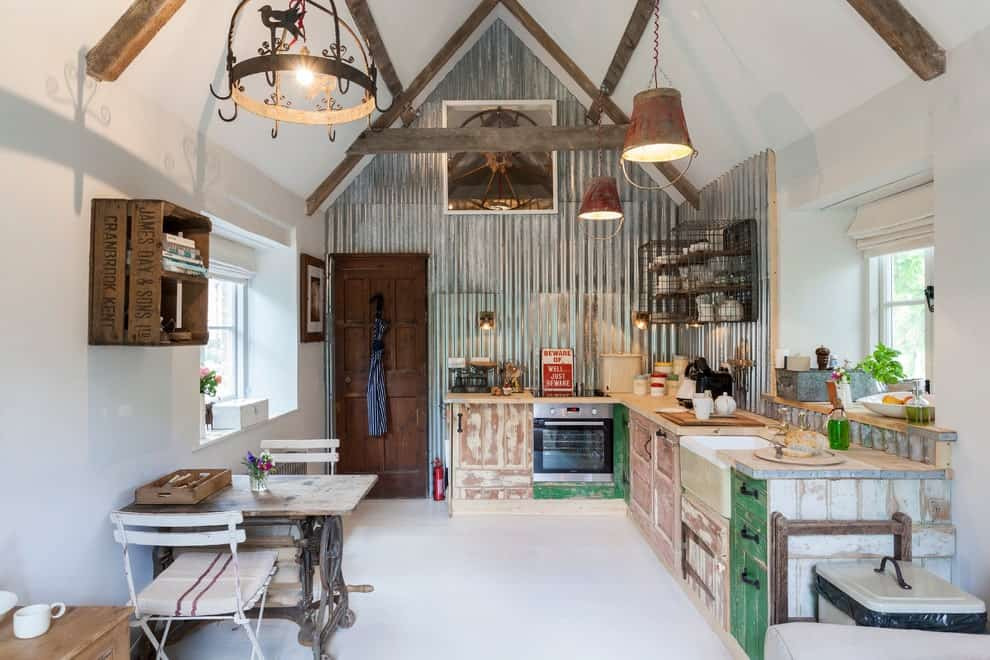 This kitchen features distressed cabinets and a rustic dining set lighted by a vintage chandelier. It has white tiled flooring and a cathedral ceiling lined with wood beams.