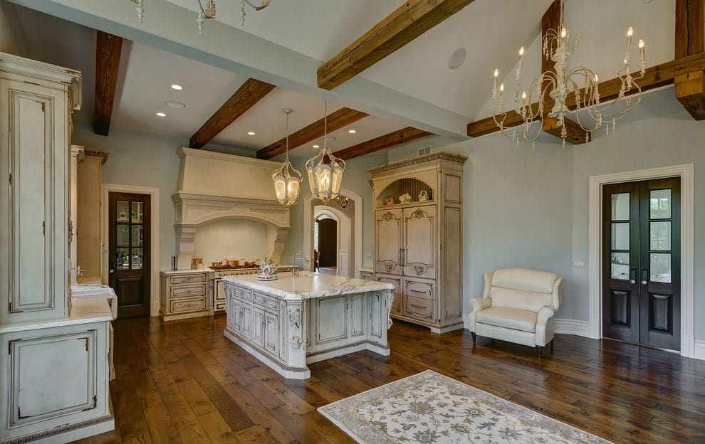 Spacious kitchen with distressed white cabinets and a matching central island topped with a white marble counter. It is illuminated by gorgeous pendants and recessed lights mounted on the wood beam ceiling.