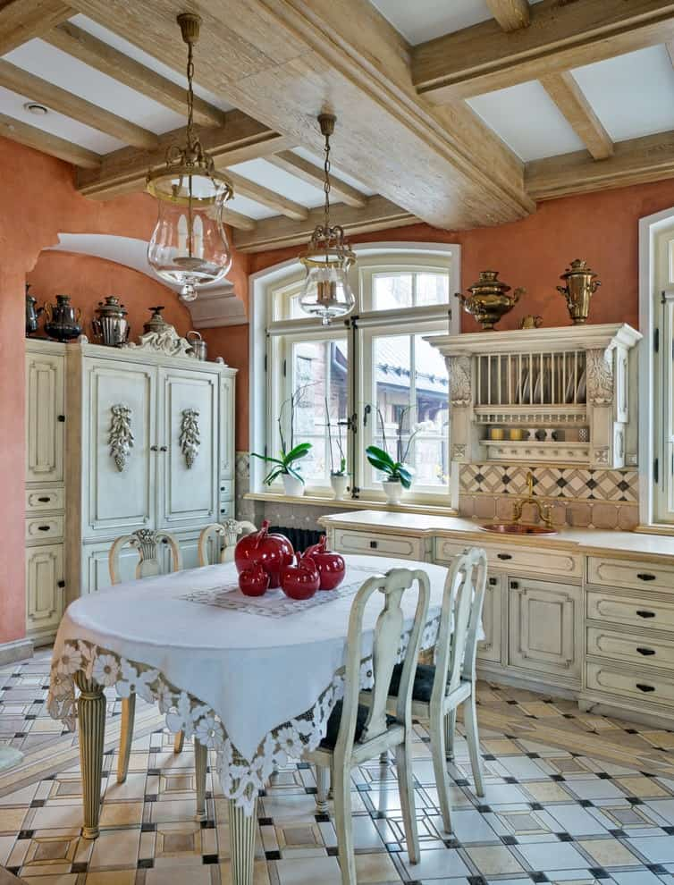 Distressed cushioned chairs sit at an oval dining table covered in a lace bordered mantle. It is accompanied by glass pendant lights and white cabinets against the coral walls.