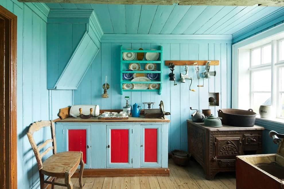 Blue cabinets accented with red doors blend in with the beadboard walls and wood plank ceiling. This kitchen has hardwood flooring and white framed windows inviting natural light in.