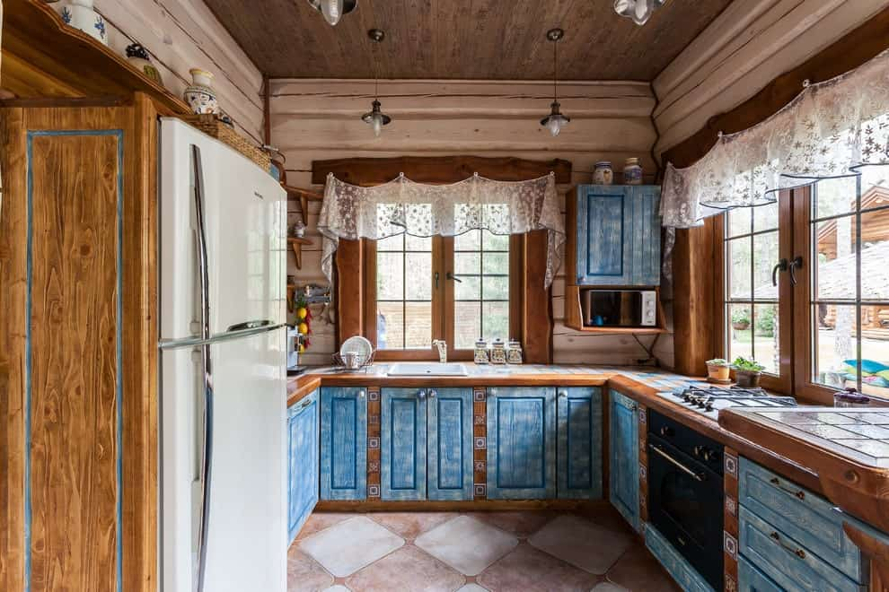 Shabby-chic style kitchen showcases blue cabinets along with contrasting black and white appliances. It has diamond tiled flooring and wooden framed windows dressed in lace valances.