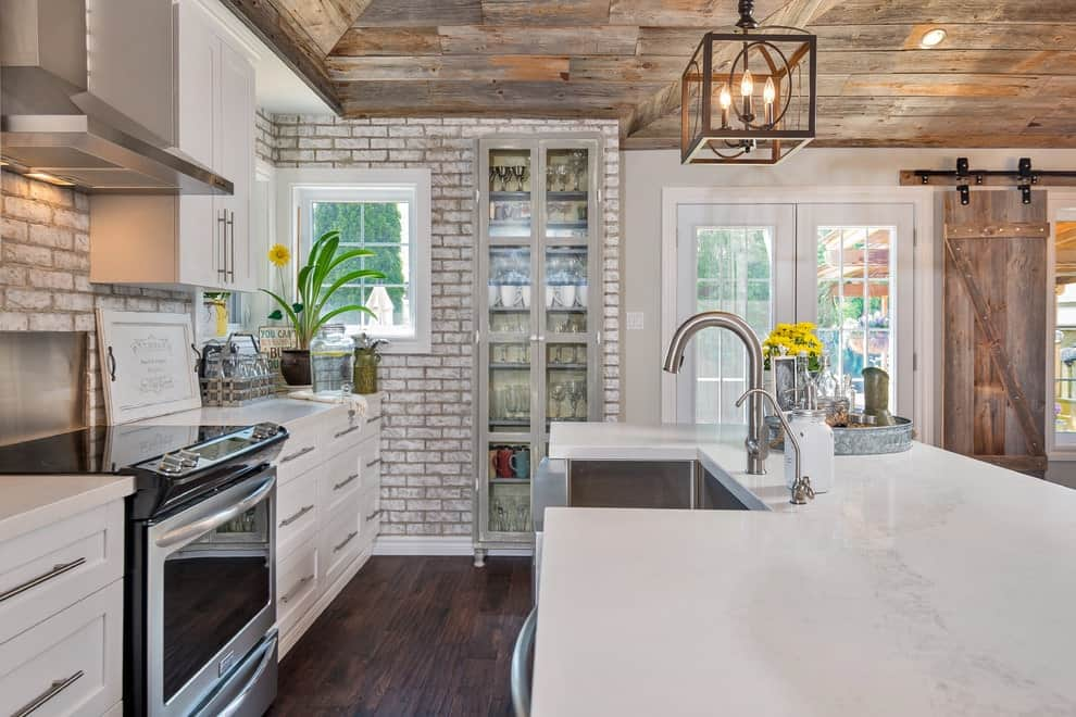 Natural hardwood flooring complements the vaulted ceiling clad in rustic wood planks. This kitchen has an immense marble top island and white cabinetry against the distressed brick walls.