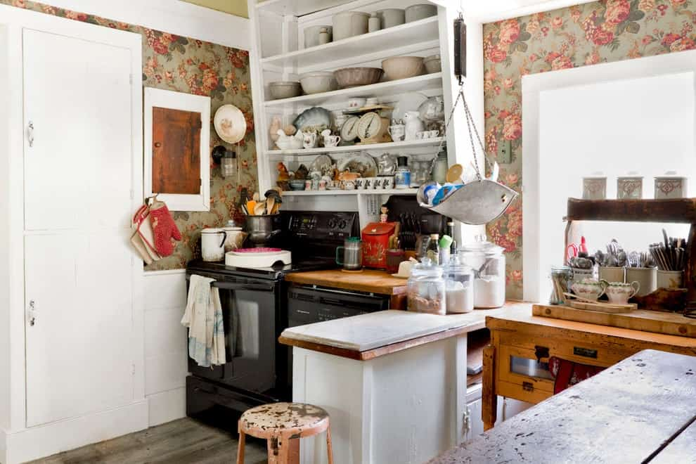 Floral wallpaper sets a charming backdrop to the white shelves and black appliances in this kitchen with wooden cabinets and a small peninsula paired with a rustic stool.