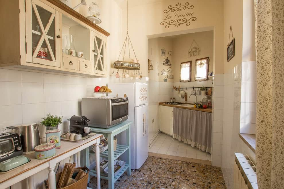 Shabby-chic style kitchen offers multi-colored appliances and storage along with a hanging round rack. It has granite tiled flooring and beige walls dominated by white backsplash tiles.