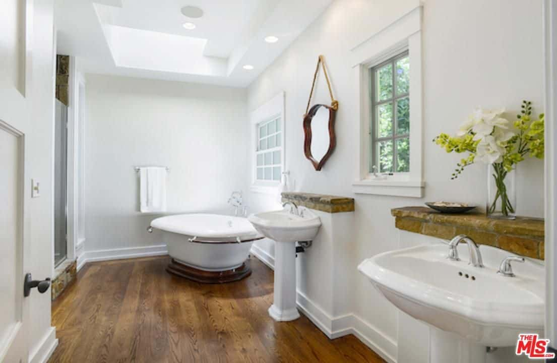 Another classic bathroom in the property featuring a free-standing bath tub, hardwood flooring, white walls and ceiling and customized glass windows.