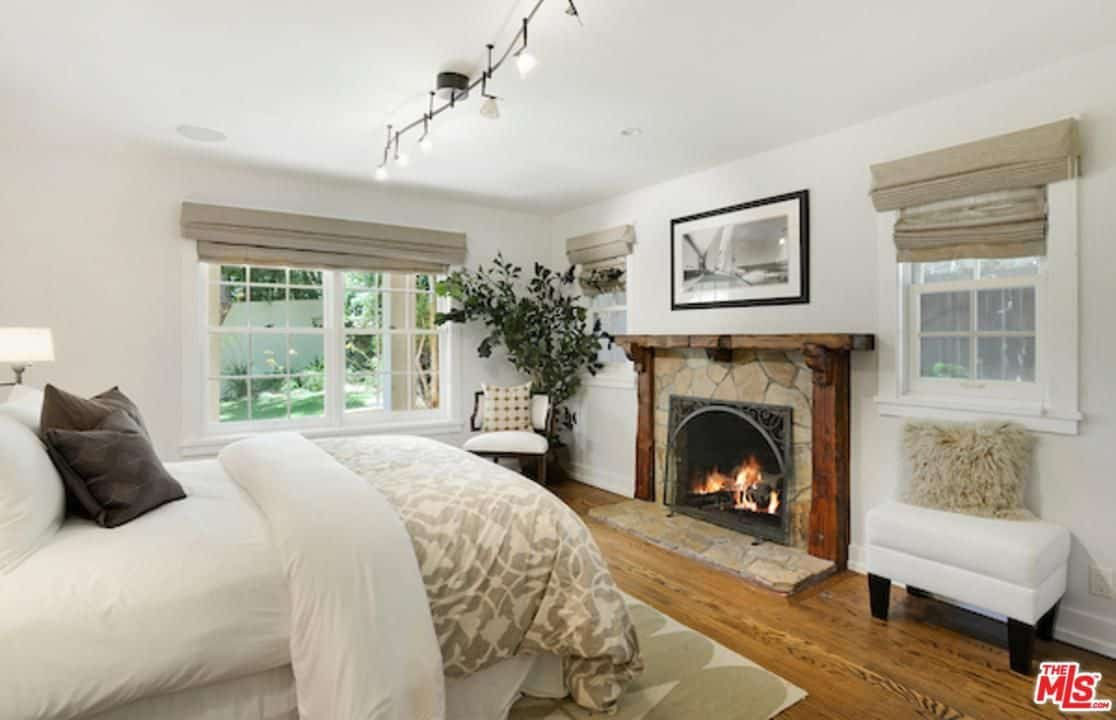 White guest bedroom offers a comfy bed and stone fireplace framed with wooden mantel. It has glazed windows and natural hardwood flooring topped by a patterned rug.