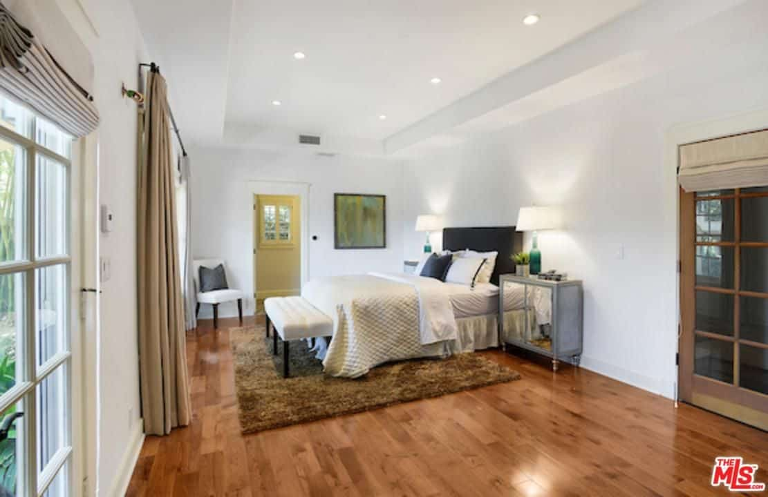 Cozy guest bedroom with modern furniture and a brown shaggy rug that lays on the rich hardwood flooring. It is illuminated by green table lamps and recessed lights mounted on the tray ceiling.