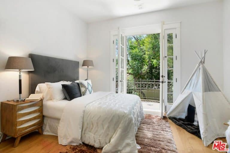 One of Alanis Morissette's house bedrooms with a glass door, terrace, table lighting and a mini tent.