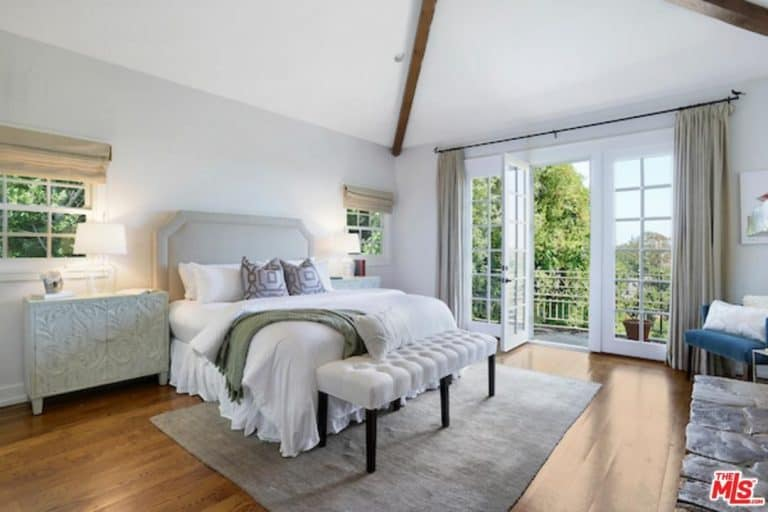 White skirted bed sits in between ornate nightstands in this living room with wide plank flooring and framed glass door that opens to the balcony overlooking a lush green yard.