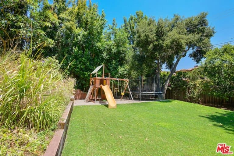 Alanis Morissette's enormous backyard has a playground surrounded with tall trees.