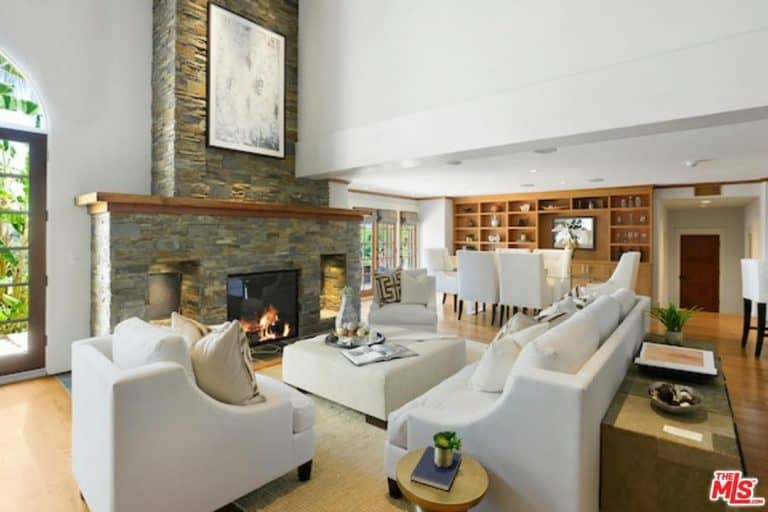 A living space featuring a large stone fireplace together with the white set of seats.