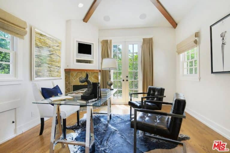 Gorgeous home office with a stone fireplace fixed on the white pillar. It includes a glass office desk surrounded with a white wingback chair and a pair of black leather chairs on a navy blue cowhide rug.