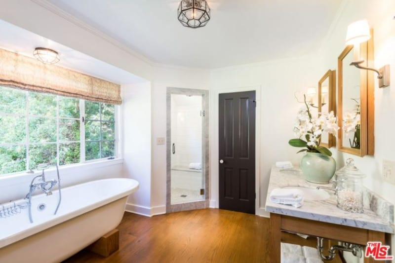 Marissa Ribisi's primary bathroom is surrounded by the white paint that matches the hardwood flooring while the freestanding tub is placed near the window.